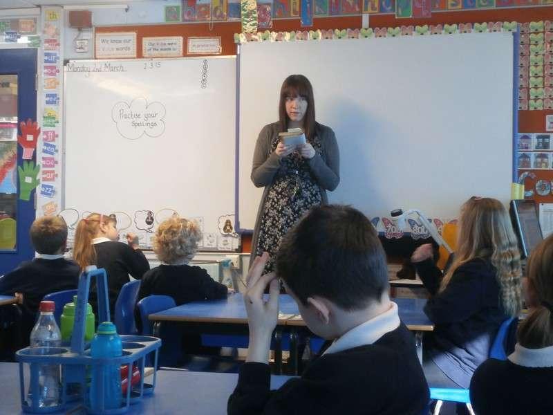 Year 5 teacher Miss Birmingham reads to Year 3 children